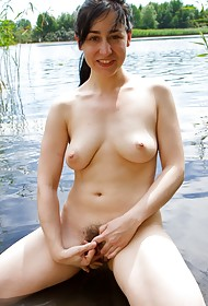 Outdoors, sunning her pale naked body by the lake Brooklyn emerges from the reeds and walks into ...
